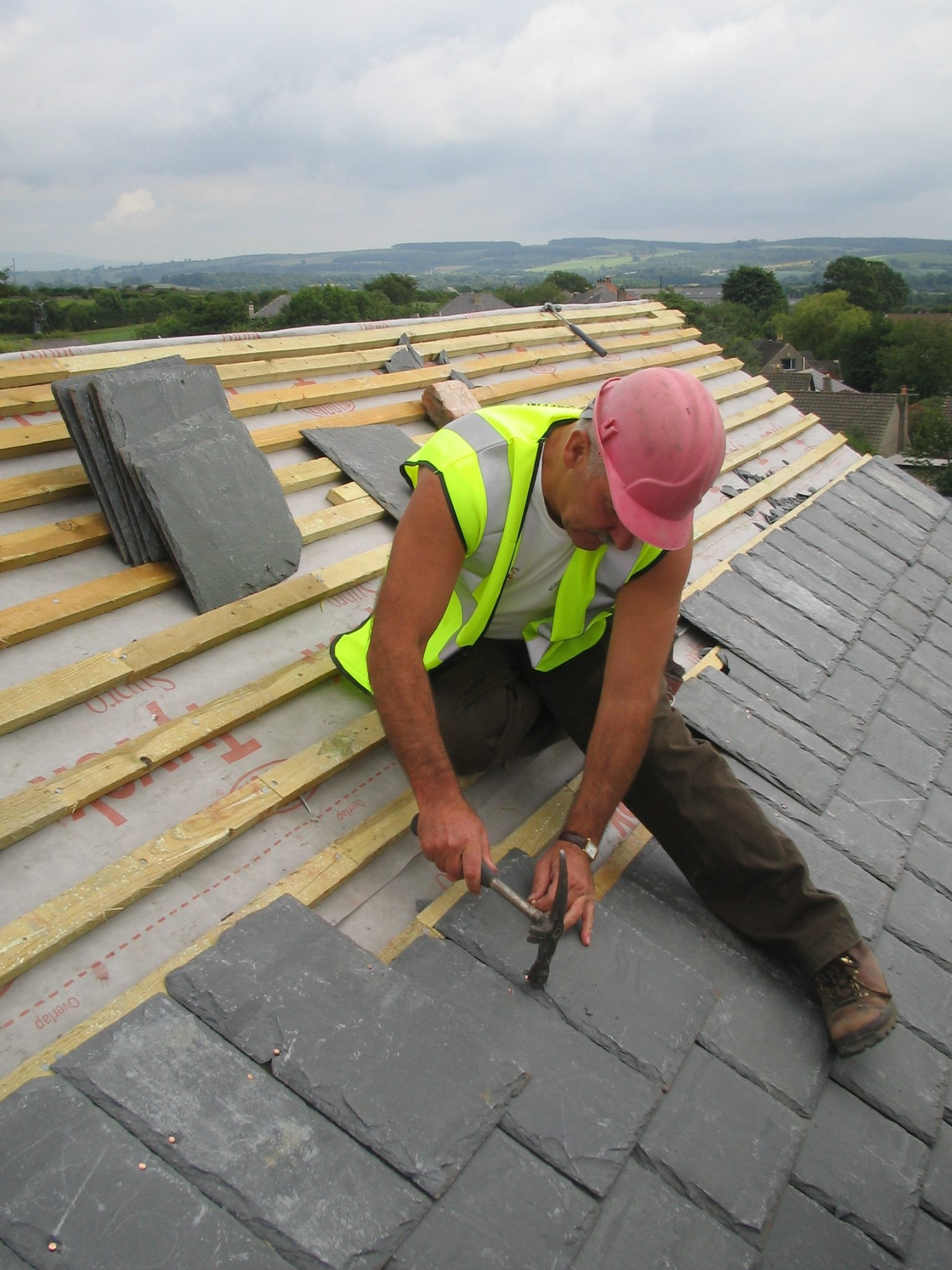Man pulling shingles on a roof